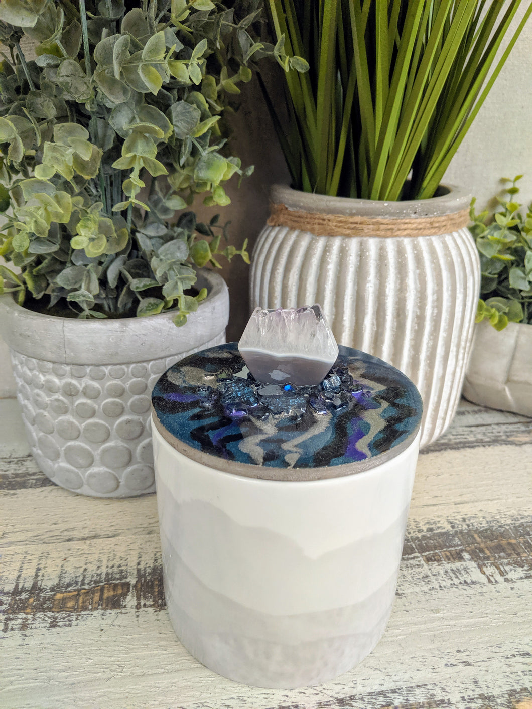 white and grey canister with blue lid and crystal stone