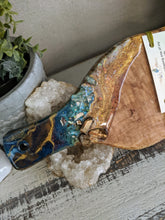close up abstract teal and gold resin cheeseboard with crystals