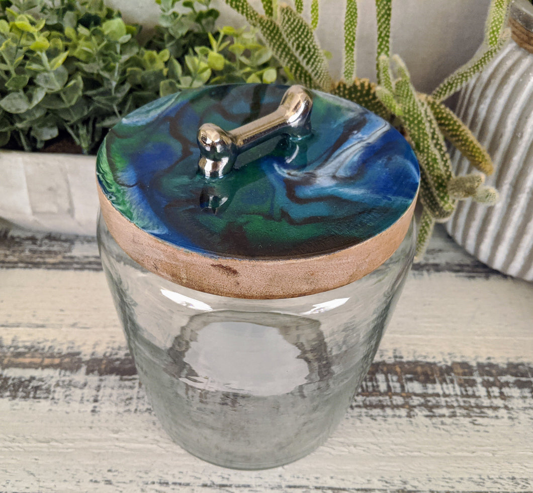 clear glass dog treat canister with wood lid coated in blue green white bronze resin with silver bone