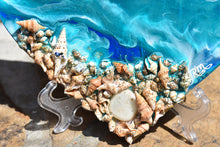close up ocean heart with shells blue teal white
