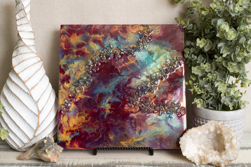 abstract crimson and teal fluid resin art with stones