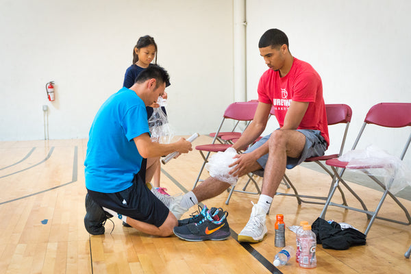 PTBA president and his daughter help Duke's Jayson Tatum with ice packs after a workout and filming session with NBA TV at the PTBA Sports Facility