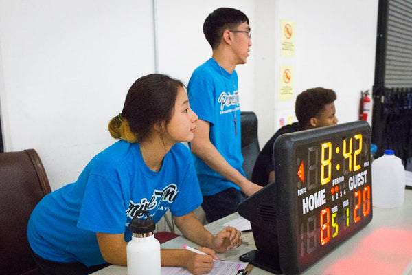 Team of PTBA scorekeepers taking stats during an youth league game