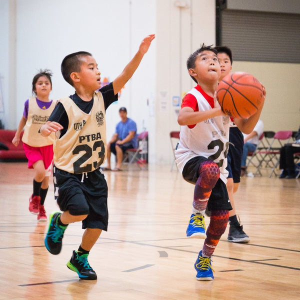 Young player attempts to defend a layup in transition during a division 9 youth league basketball game.