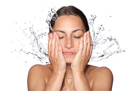 A woman splashes water on her face