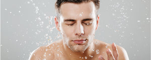 Man splasing water onto his stubble and skin.