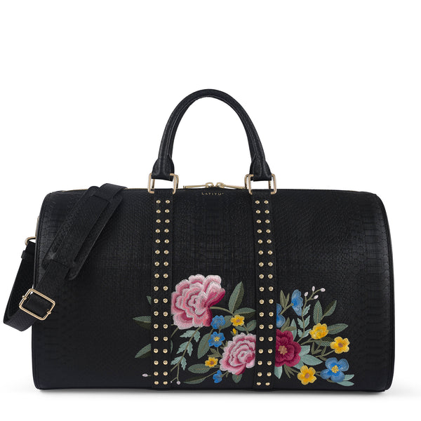 Front view of Latitu° Jardin de København holdall in black with floral embroidery, and shoulder strap