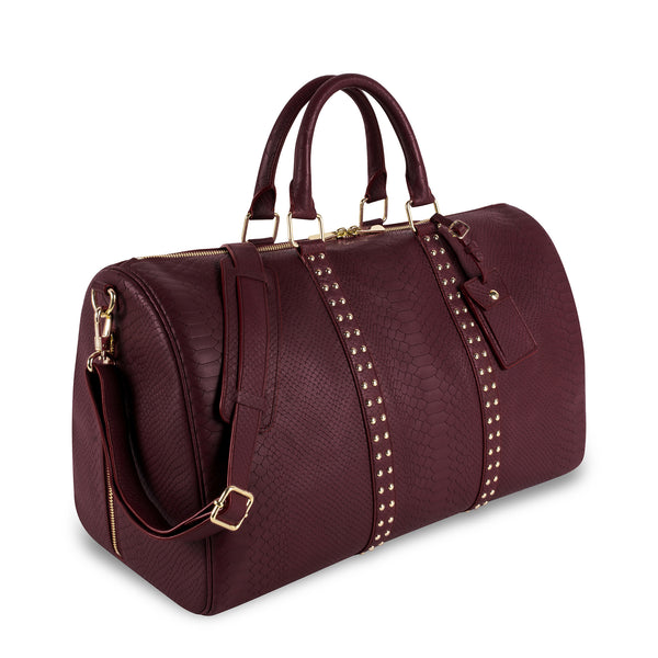 Three quarter view of Latitu° København holdall in burgundy, and shoulder strap
