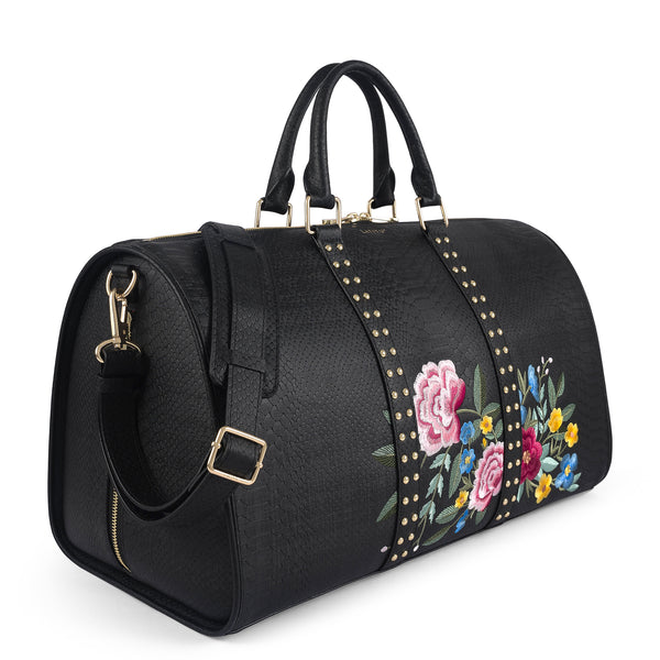 Three quarter view of Latitu° Jardin de København holdall in black with floral embroidery, and shoulder strap