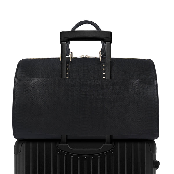 Black Latitu° København holdall attached to luggage using built-in suitcase strap
