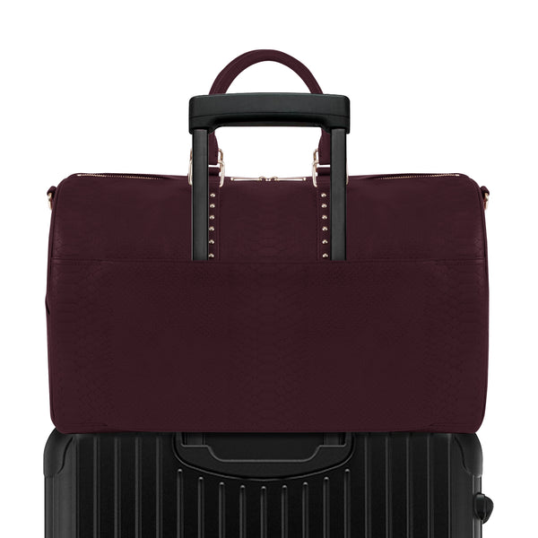 Burgundy Latitu° København holdall attached to luggage using built-in suitcase strap