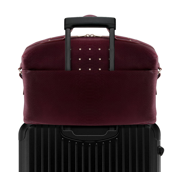 Burgundy Latitu° Venezia weekender attached to luggage using built-in suitcase strap