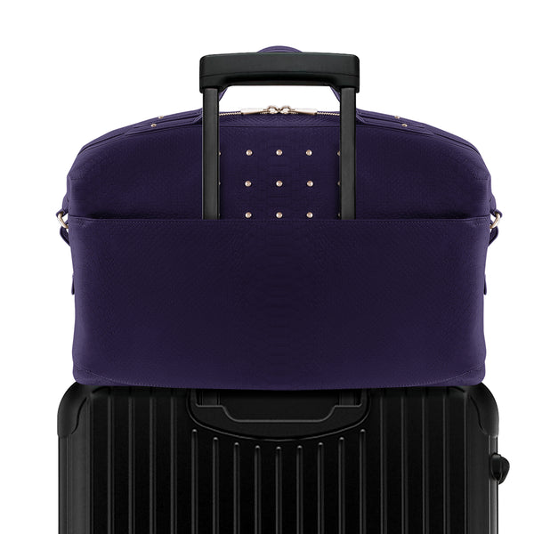 Royal purple Latitu° Venezia weekender attached to luggage using built-in suitcase strap