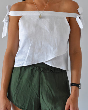 white linen tie off shoulder top. green silk shorts
