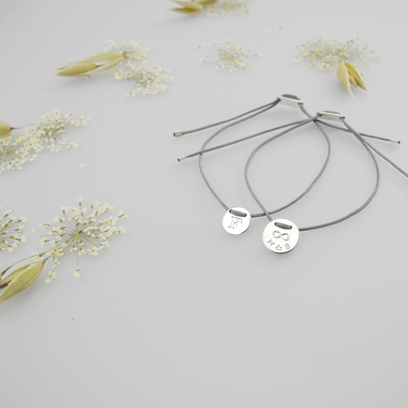 delicate and handmade bracelet out of 925 sterling silver and a durable and colorfast nylon cord. The engraving on this pendant contains one initial. This collection features an array of personalized bracelets. Every piece is made to order.