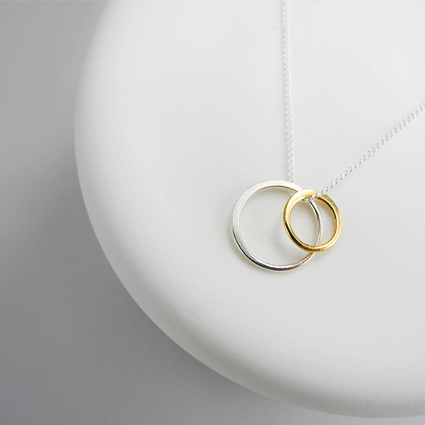 A delicate duo of two eternity rings on a simple link chain exudes sophistication and elegance. The circle pendant represents infinity, a powerful symbol of continuous connection, love, life, grace and energy.