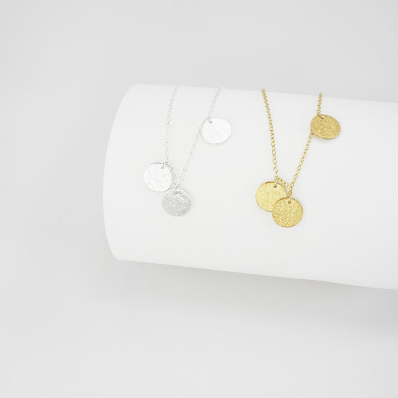 Alternating seven small tags creates a simple but extravagant design. This asymmetrical necklace is a modest statement piece. The brushed surfaces add a dazzling touch to these timeless pendants.