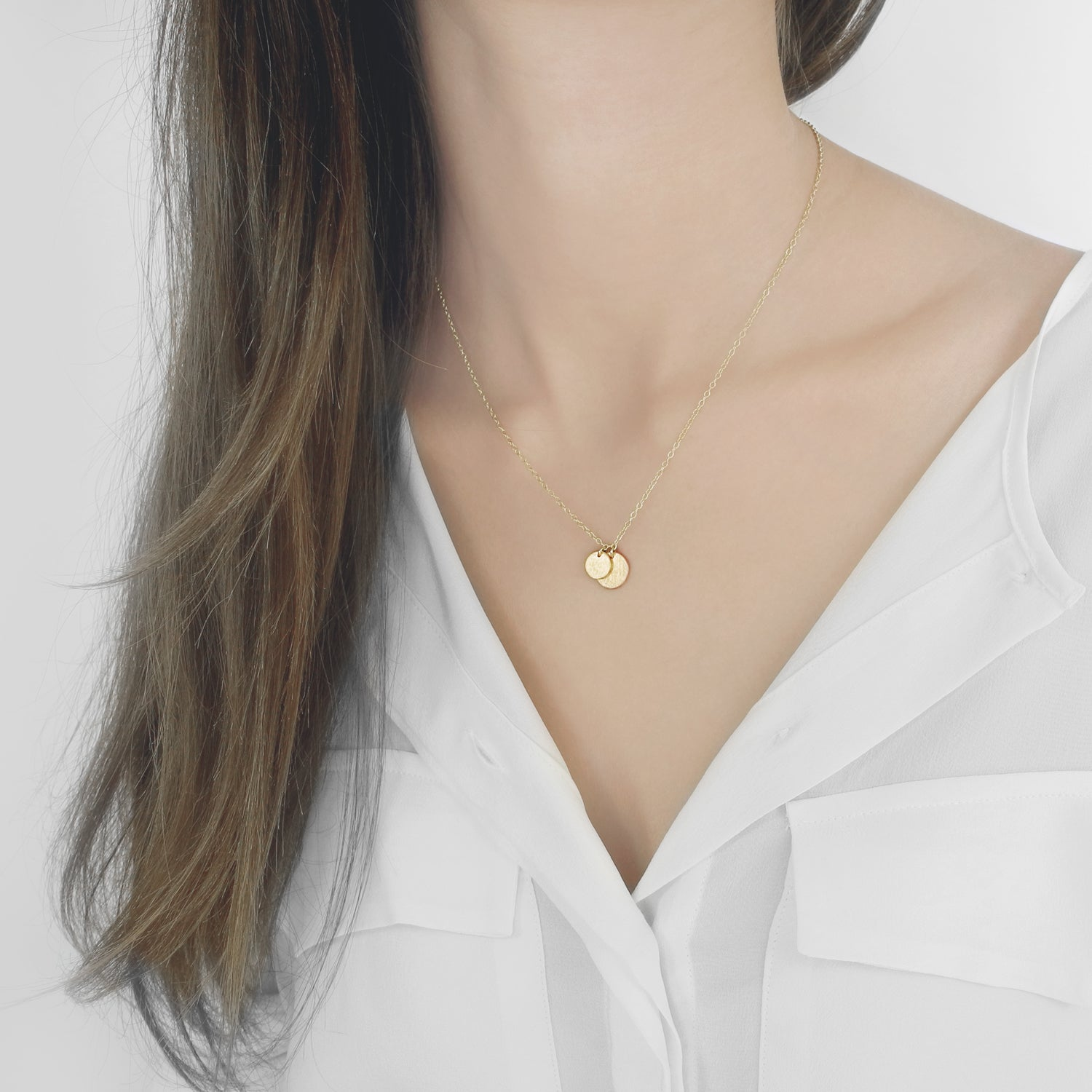 A delicate duo of round tags on a simple link chain exudes sophistication and elegance. The brushed surfaces add a dazzling touch to these timeless pendants. Classic and captivating, this necklace is striking in its simplicity.