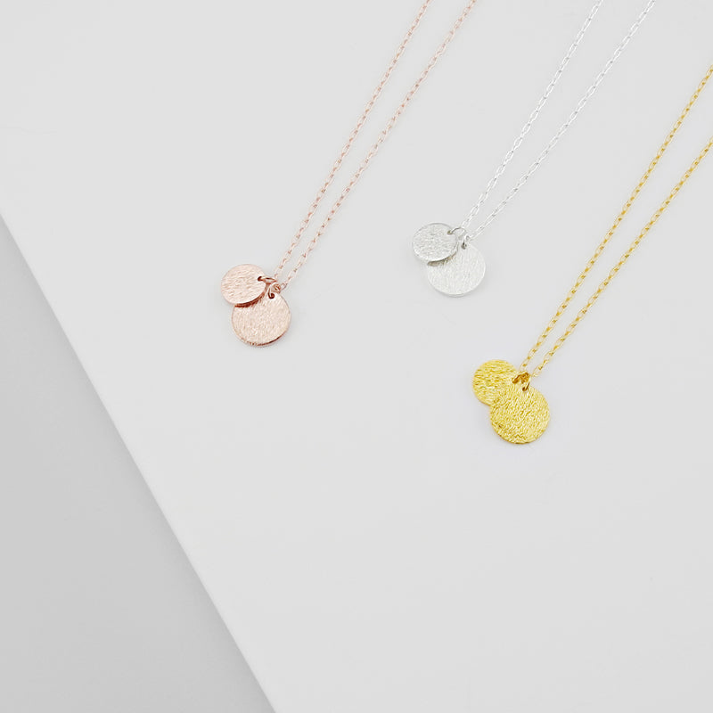 A delicate duo of round tags on a simple link chain exudes sophistication and elegance. This necklace is available in 925 sterling silver, 20k Gold plated and Rosegold plated.