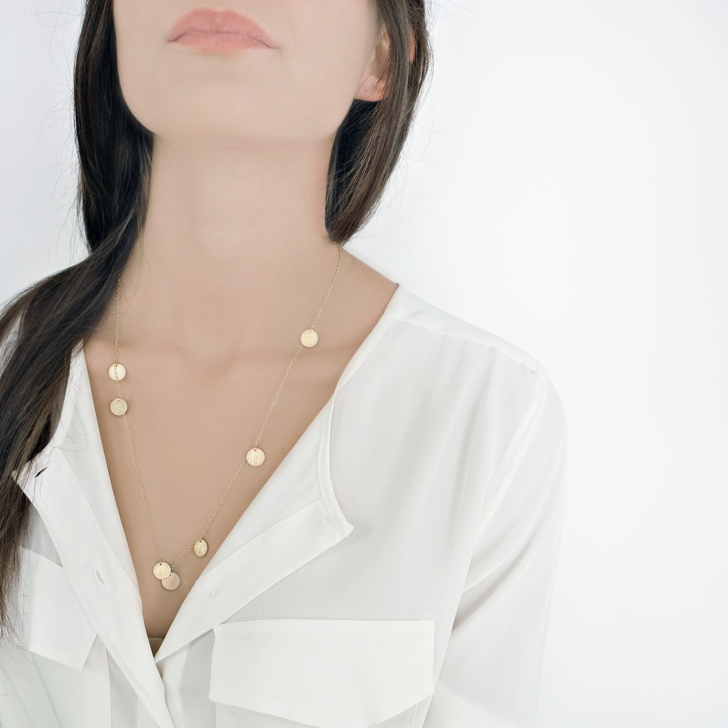 Alternating seven small tags creates a simple but extravagant design. This asymmetrical necklace is a modest statement piece.