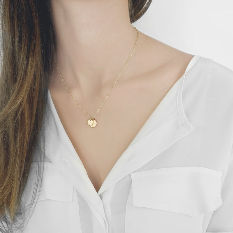 A delicate duo of round tags on a simple link chain exudes sophistication and elegance. Classic and captivating, this necklace is striking in its simplicity.