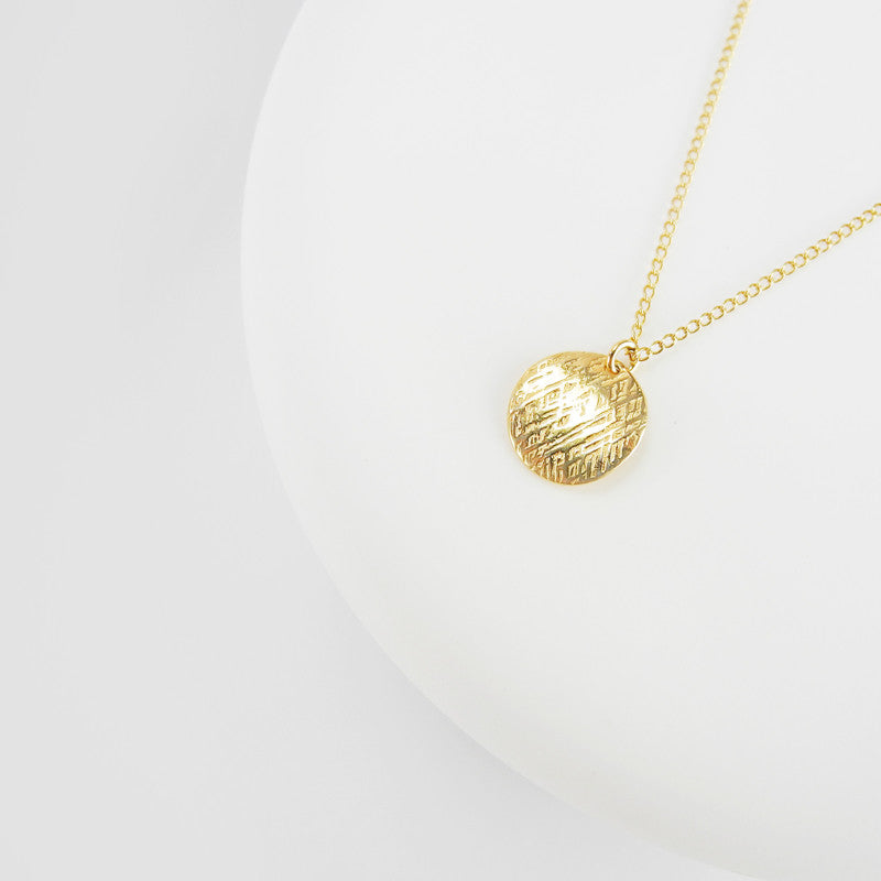 This simple sequin pendant exudes understated elegance. The subtle textured surface and the slightly domed shape adds dimension to this classic style.