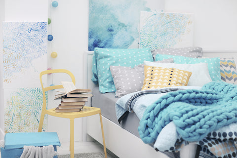 Bedroom with yellow and blue decor, patterned pillows, and watercolor wall art