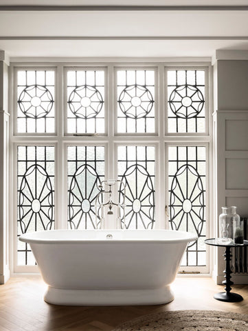 Victoria and albert york soaking tub model YOR-N-SW+YOR-B-SW against a decorative window in a bathroom