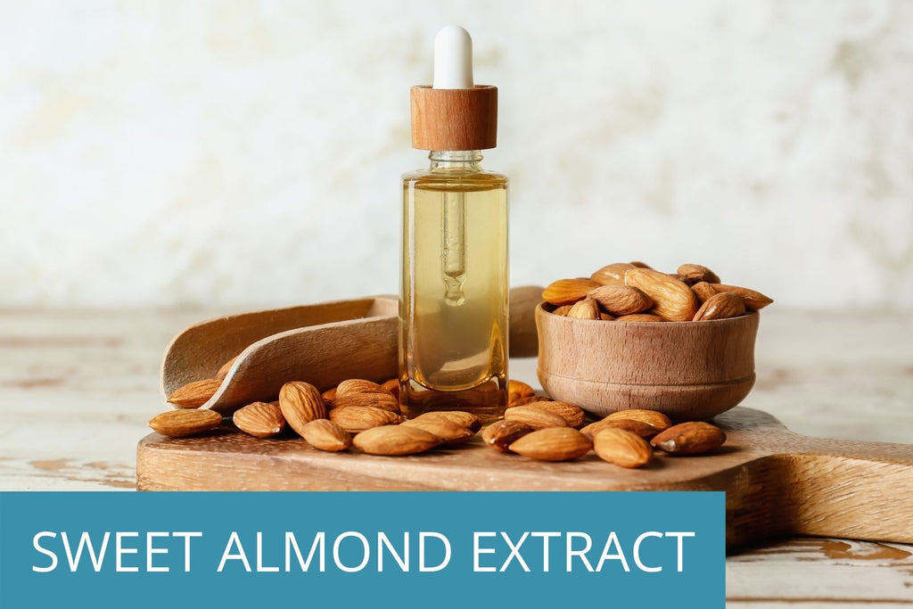 several fresh almonds next to a glass bottle of almond extract - a key ingredient in TEENOLOGY products to boost hair and skin health