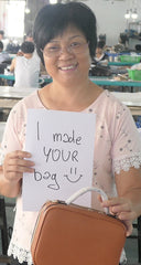 "Loretta, one of FERRON's factory worker holding ""I made your bag"" sign"