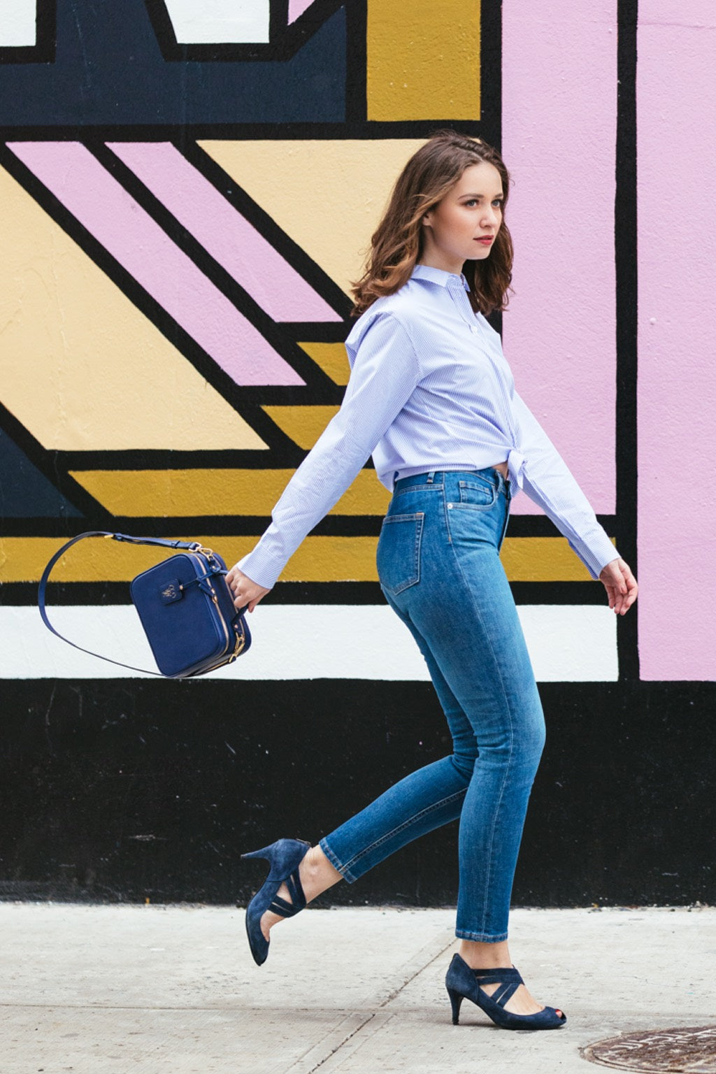 Model holding the crossbody bag by handle
