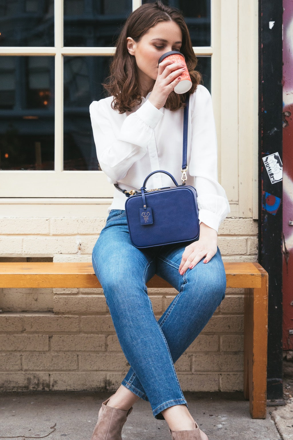 Model wearing FERRON crossbody vegan handbag and drinking coffee