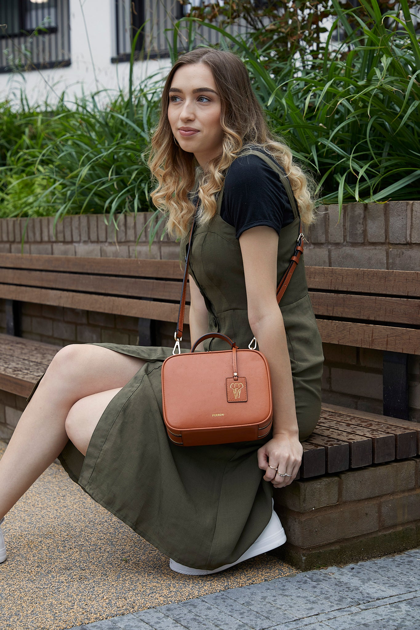 Model sitting wearing FERRON Vegan Signature Crossbody bag in tan with adjustable and detachable straps