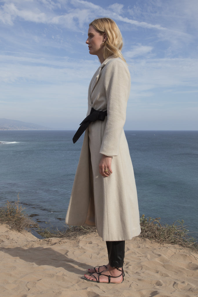 Model wears BELTED VULCAN COAT - IVORY by Heidi Merrick (Side)