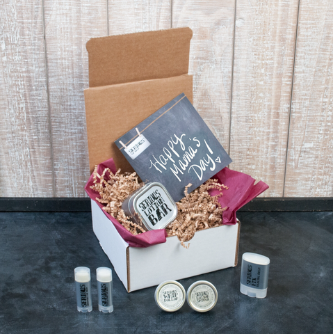 White box with brown crinkle paper and an assortment of all natural and handmade lip care and skin care products on a black surface with wood background
