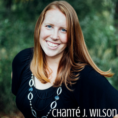 Image of Chanté J. Wilson - She has red hair, a black shirt with oval shaped beads on a necklace. She is standing in front of greenery.