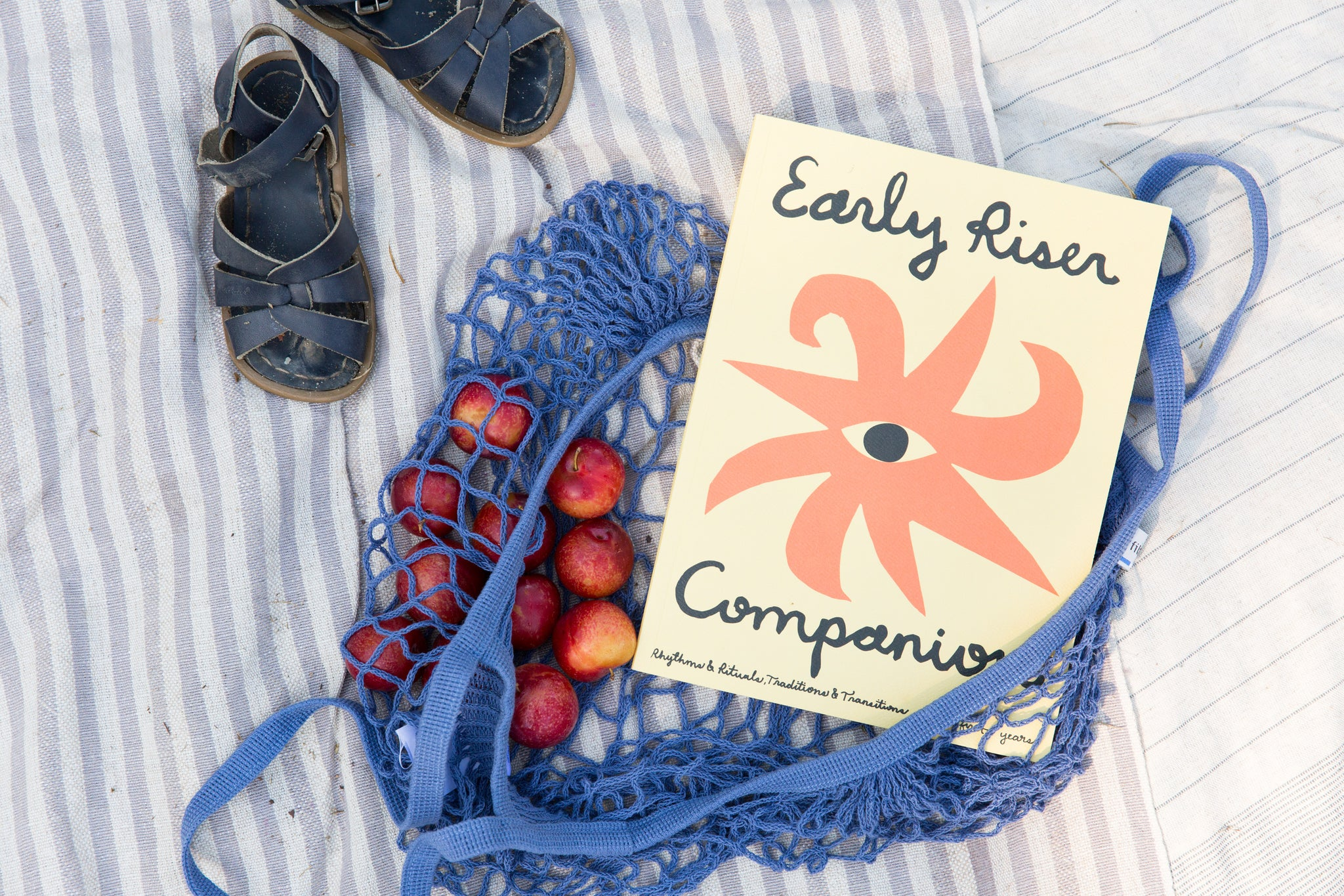"mini market bag with kid's sandals and ""Early Riser Companion"" book"