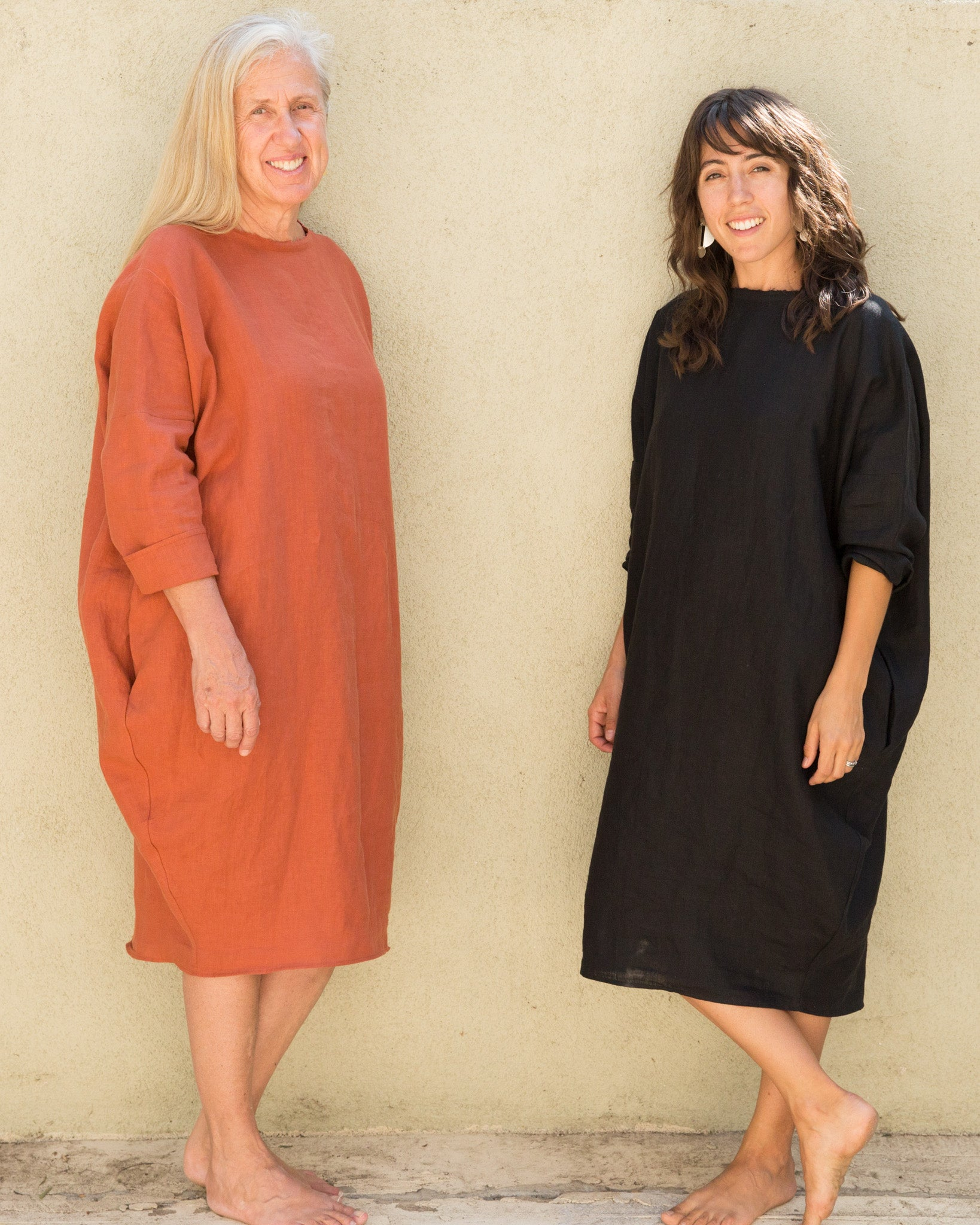 Dotter owners, Susanne McLean and Annika Huston, wearing Robyn King dresses in front of green wall