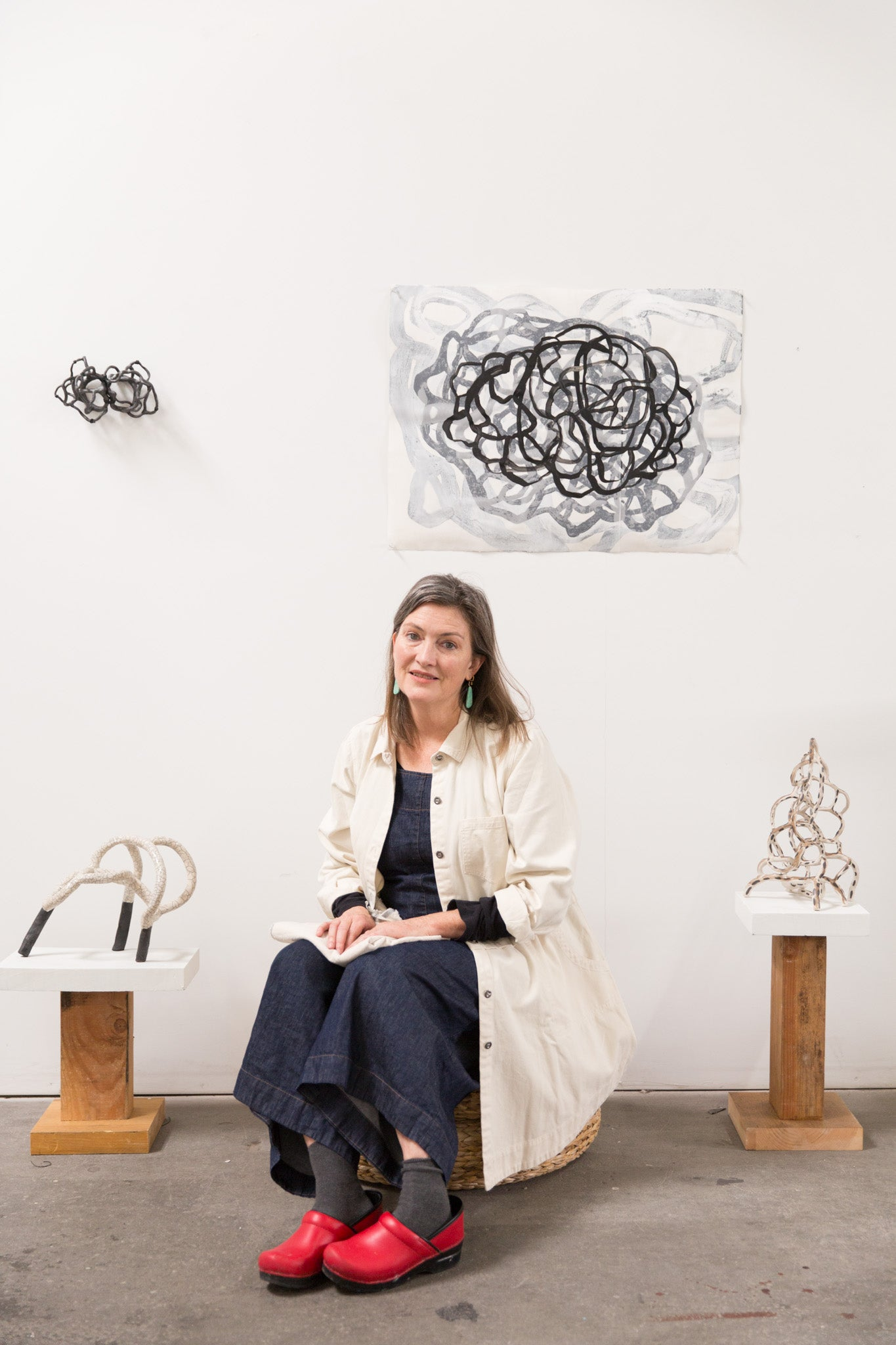 artist Laura Cooper seated in studio surrounded by her sculptures