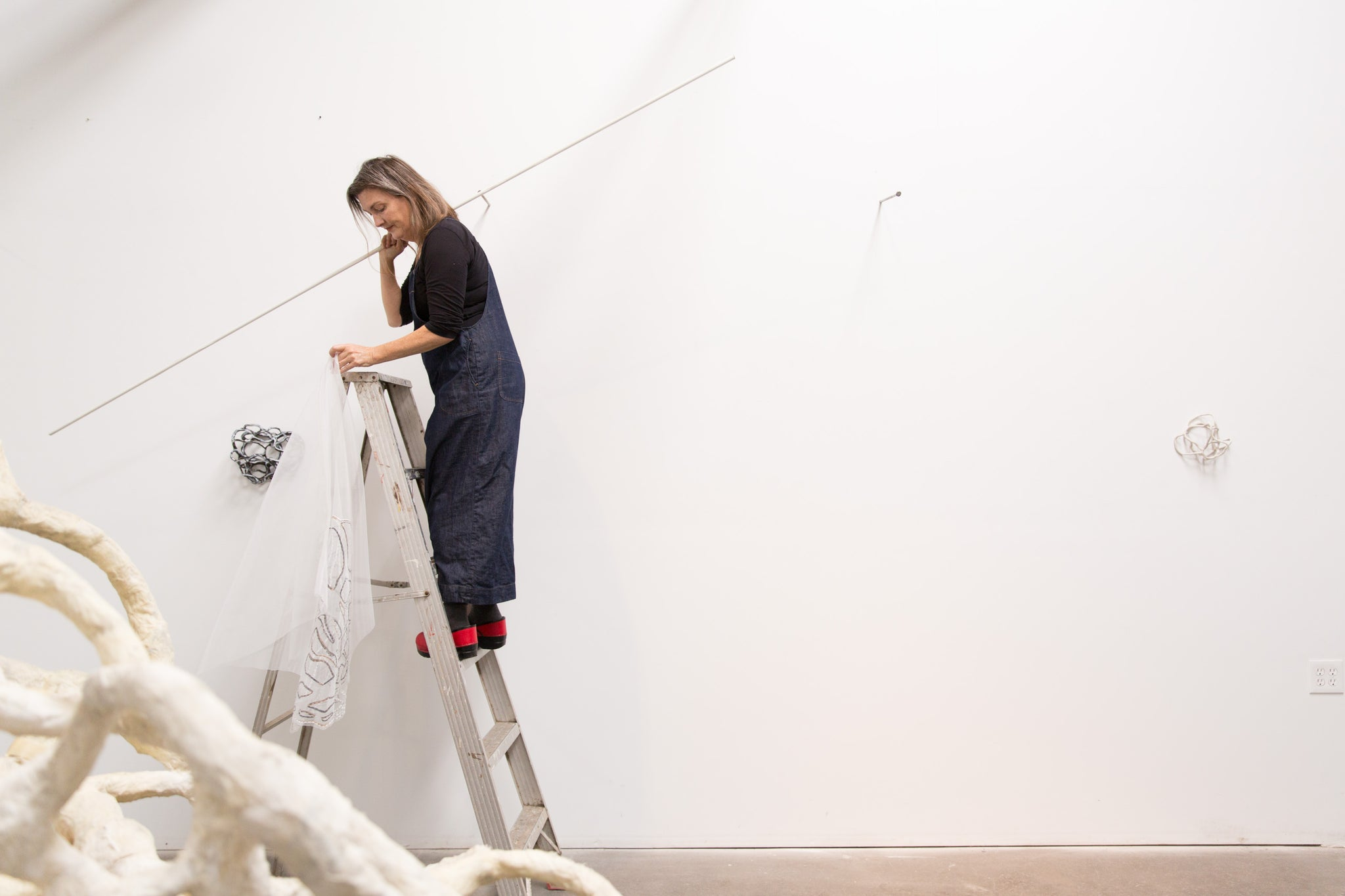 artist, Laura Cooper, on ladder installing artwork