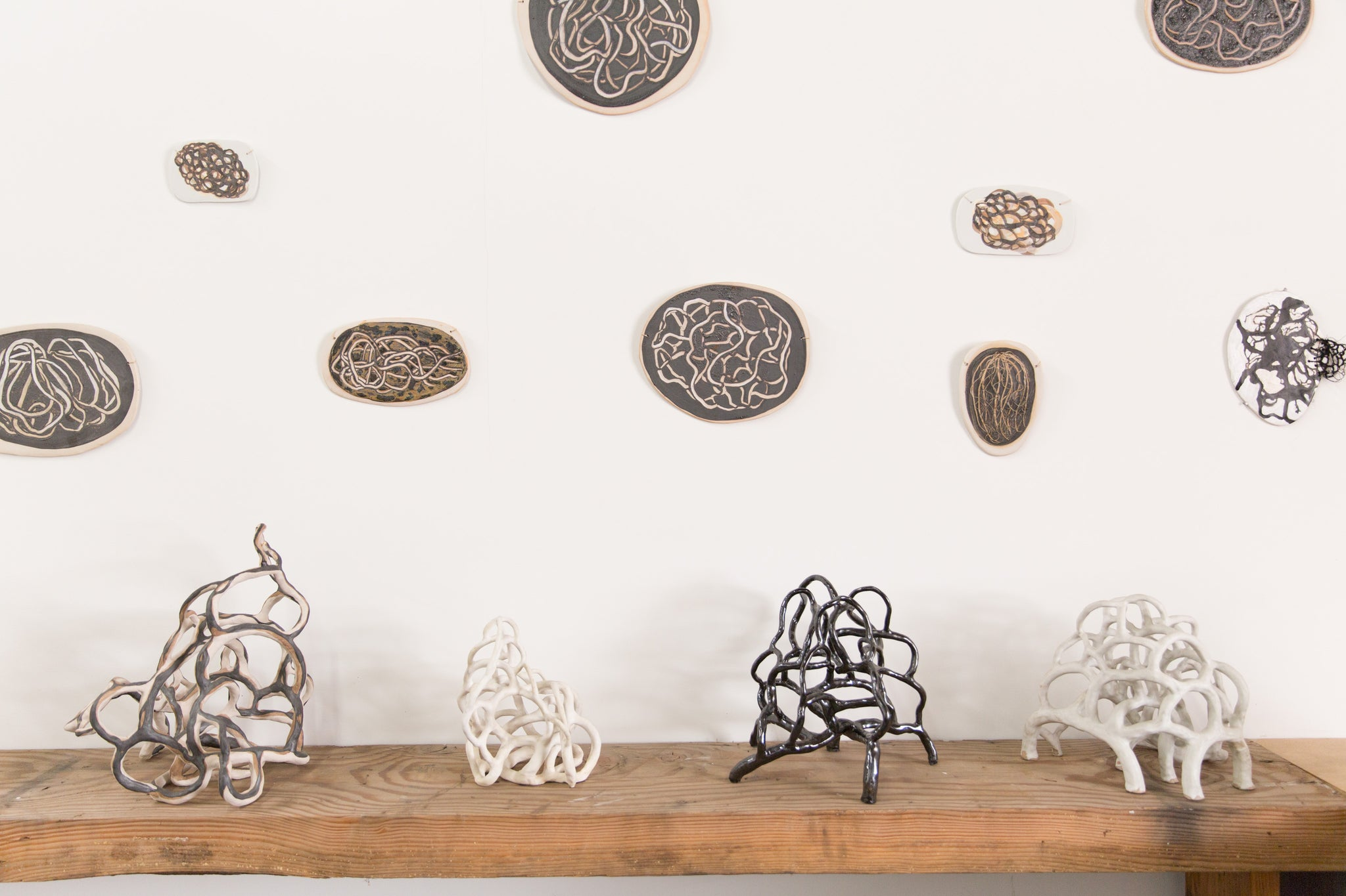 ceramic artworks by Laura Cooper hung on wall and on standing on table