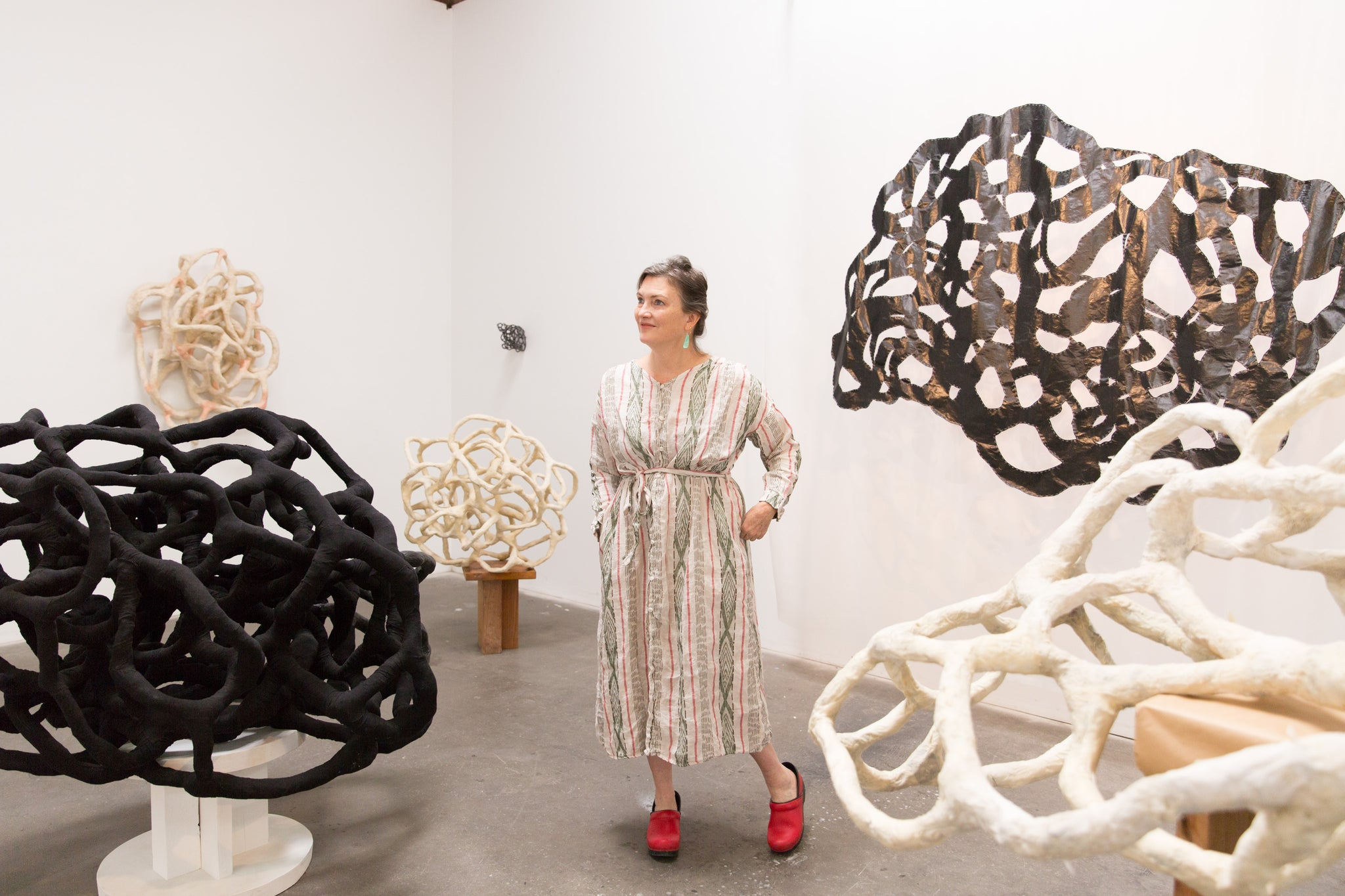 artist, Laura Cooper, surrounded by her sculptures in Los Angeles studio