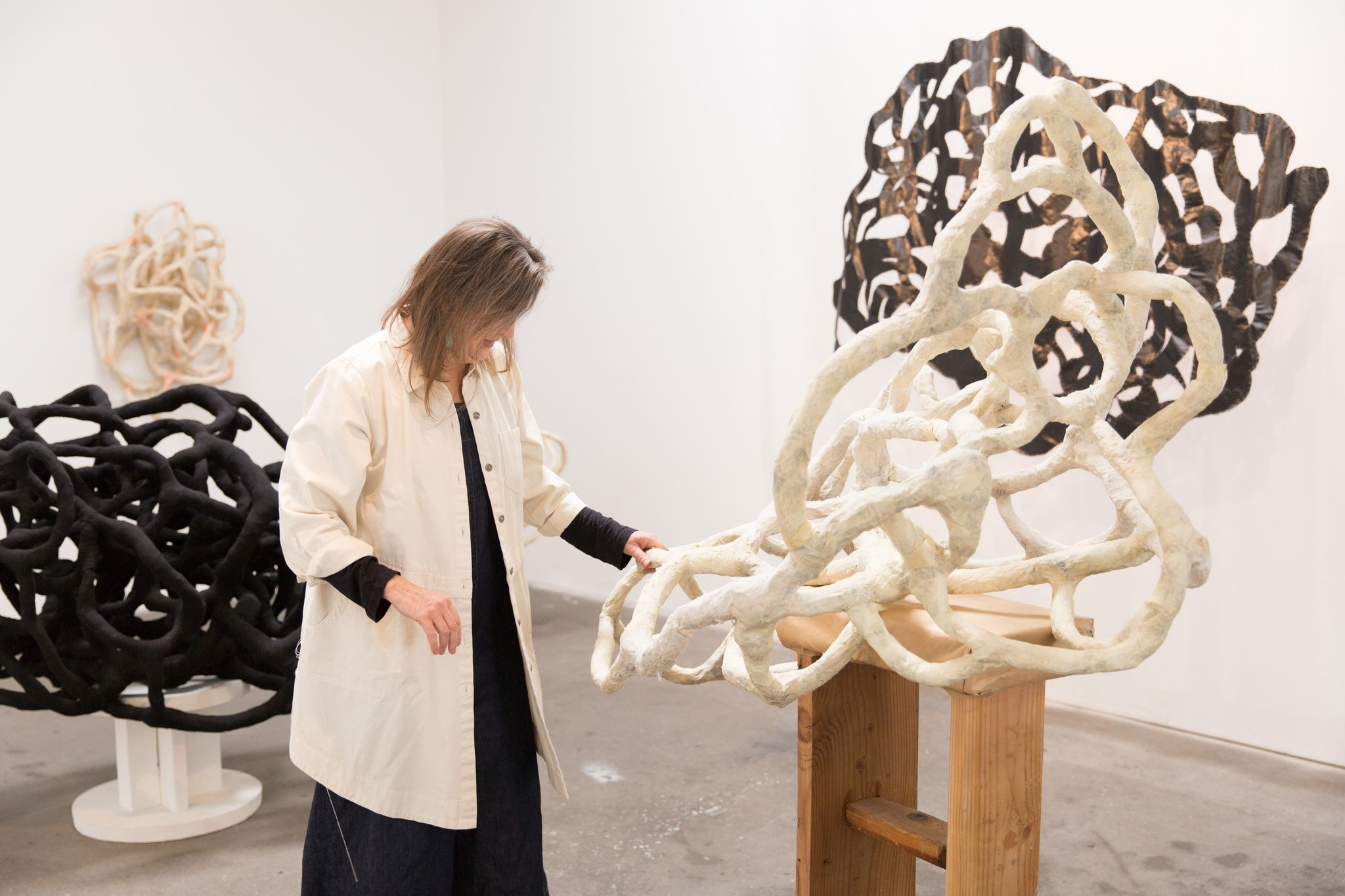 artist, Laura Cooper, touching her sculpture
