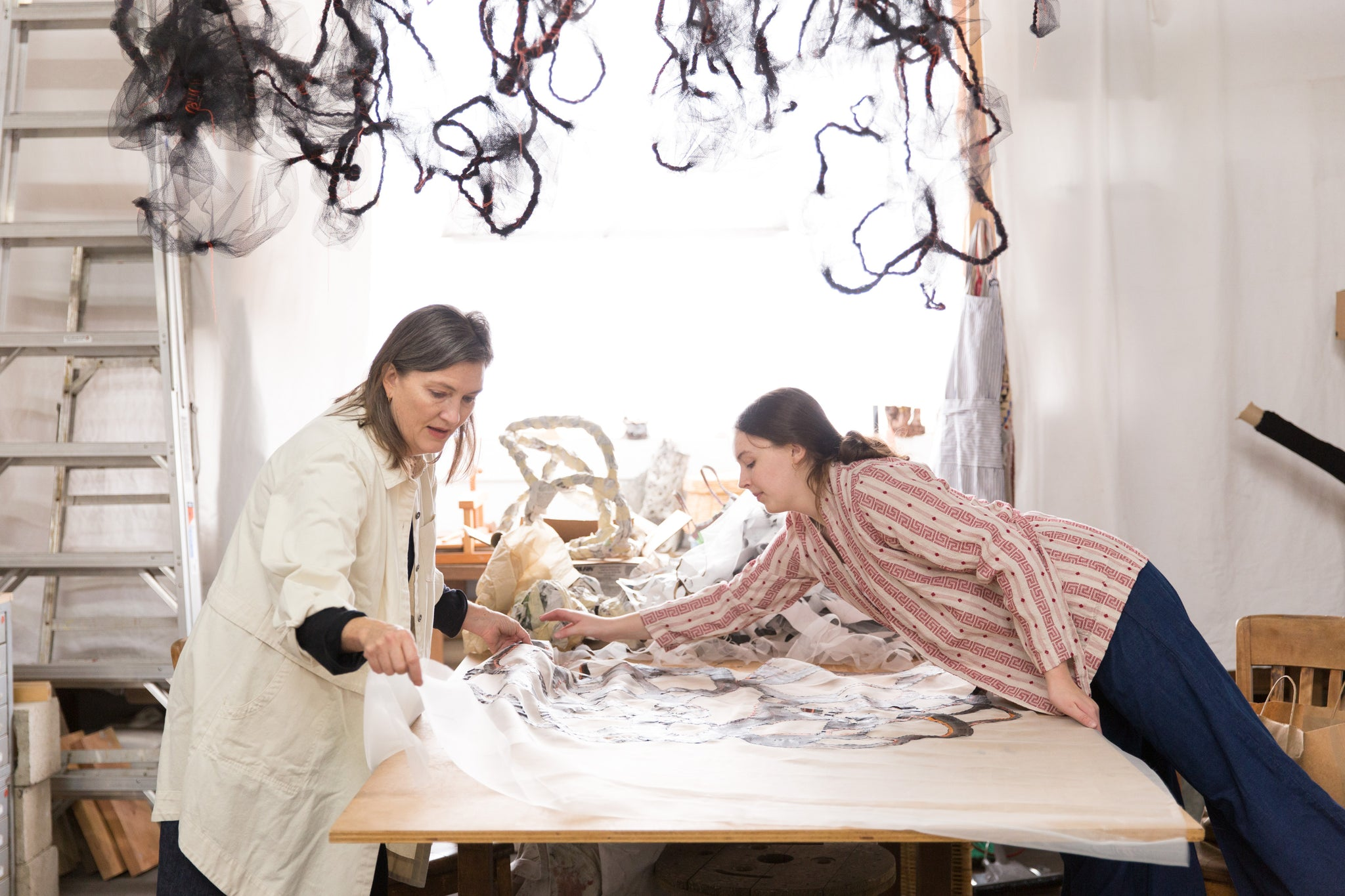 artist Laura Cooper and her daughter at table in artist's studio