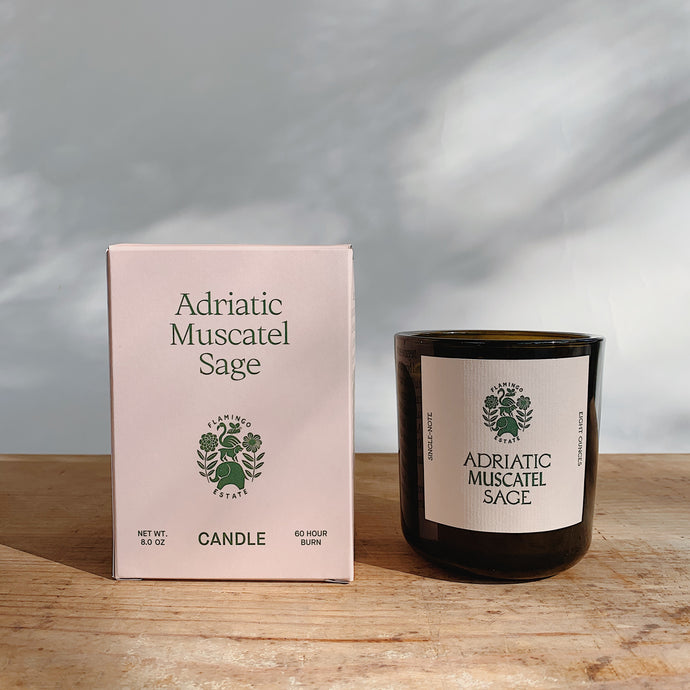 Adriatic muscatel sage candle next to its pink packaging.