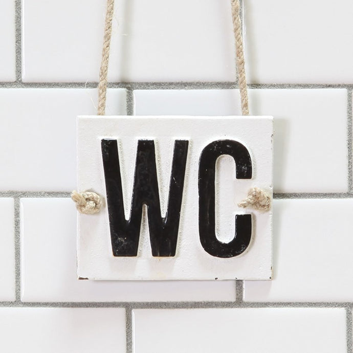 Front view of WC cast iron sign hanging from cotton rope.