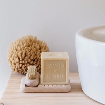 Side view of beech wood soap dish holding a nail brush and square bar of soap