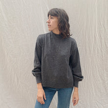 Load image into Gallery viewer, front view of model looking sideways wearing SWTR's grey mock neck sweater