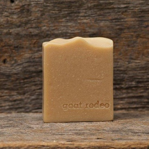 A yellowish, brown bar of soap sits on a wooden board with the brand name Goat Rodeo stamped into the soap.
