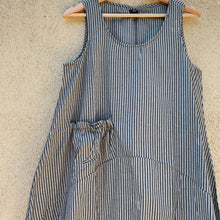 Detail of the Tulip grey striped dress hanging on a hanger.